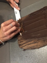 A l'aide d'un grand couteau pousse le chocolat du bas vers le haut pour former des copeaux