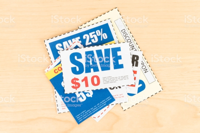 Saving discount coupon voucher on wooden desk, coupons are mock-up